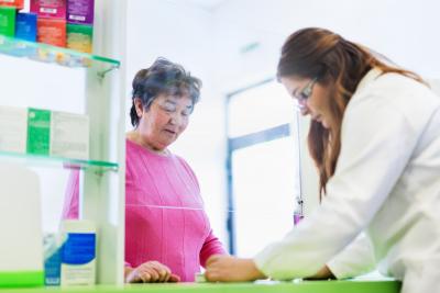 pharmacist discusses prescription medication with senior customer at pharmacy